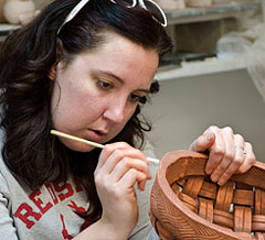 Putting the finishing touches on a handbuilt clay basket.