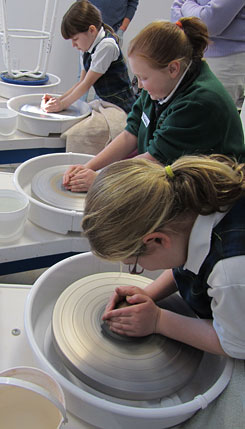 Girl Scouts work on the pottery wheel while earning their Ceramics & Clay badge.
